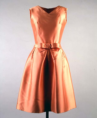 Jackie Kennedy's apricot silk ziberline dress she wore for the boat ride on lake Pichola, Udaipur India, 17 March 1962, designed by Oleg Cassini, sleeveless knee length featuring v neckline bodice and a line skirt with bow detail at waist.